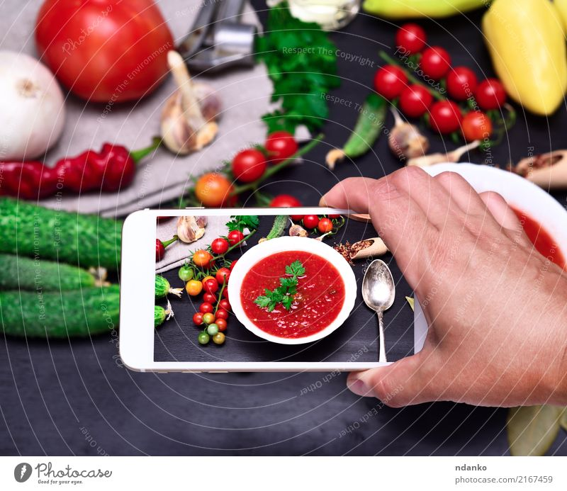 smartphone in the human hand Vegetable Soup Stew Nutrition Lunch Dinner Vegetarian diet Diet Plate Spoon Table Kitchen PDA Hand Wood Fresh Red White Tradition