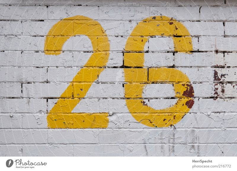 26 Manmade structures Wall (barrier) Wall (building) Brick Digits and numbers Yellow White Dye Paintwork Flake off Furrow Colour photo Exterior shot