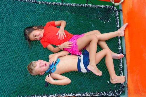 Cute kids on a boat trip. Boy is playing a toy guitar and sings for his beautiful girlfriend. Lying on catamaran's hammock, legs are intertwined. View from above