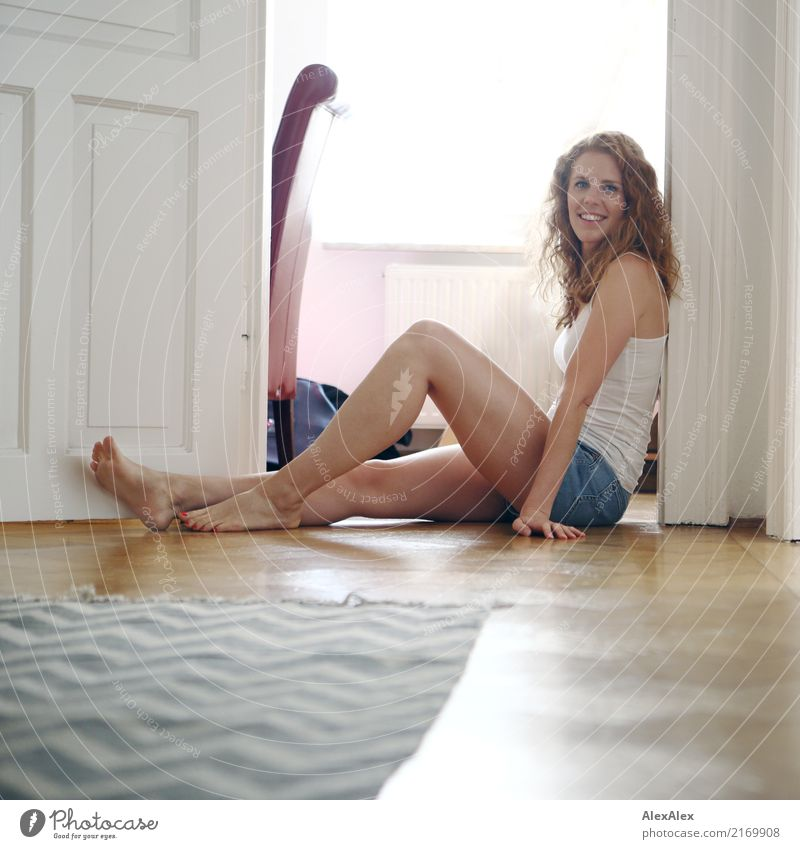 Portrait of a young, red-haired, sporty woman in hot pants, sitting on the floor in the hallway and smiling Style luck already Harmonious Well-being