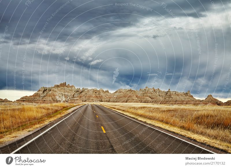 Scenic road in Badlands National Park with stormy sky. Vacation & Travel Landscape Mountain Street Sadness Lanes & trails Freedom Moody Trip Adventure USA