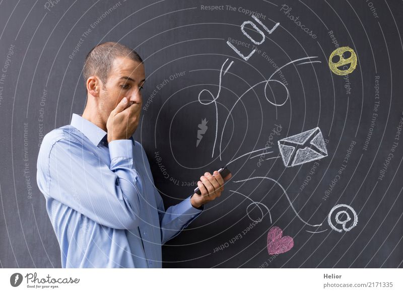 Man with mobile phone in front of chalk-drawn social media symbols on a blackboard (Topic: Social Media Overload) Lifestyle Joy Cellphone PDA Internet Masculine