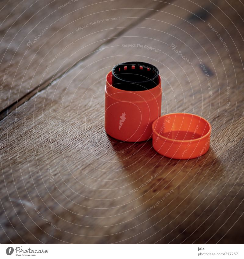coiled Tin Plastic container Containers and vessels Keep Film industry Negative Wood Brown Black Orange Analog Colour photo Interior shot Deserted