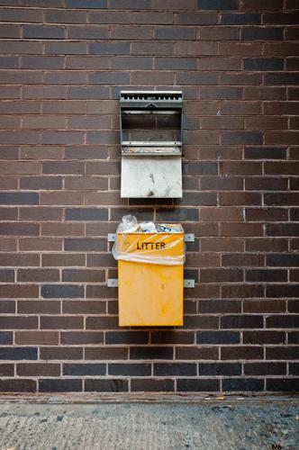 English garbage can on a wall Town Downtown Dirty Yellow Trash Trash container Dustman Refuse disposal Waste utilization Waste management Wall (building) Brick
