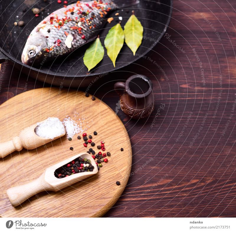 fish carp in a black frying pan Fish Seafood Herbs and spices Pan Spoon Kitchen Wood Fresh Brown Carp salt pepper cooking Dish Ingredients Colour photo Deserted