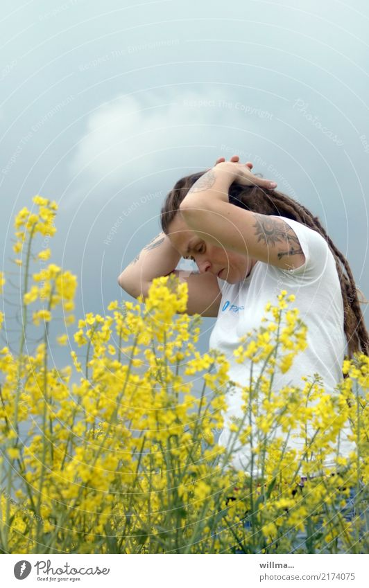 Young tattooed woman with Rastas in blooming rape Young woman Canola field Tattoo Youth (Young adults) Human being spring Oilseed rape flower Long-haired