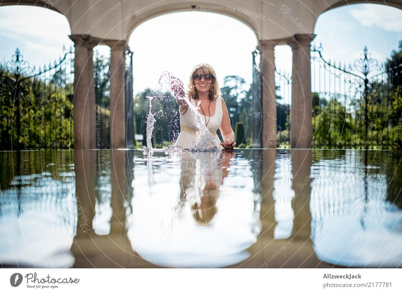 Woman with sunglasses plays with water Day Reflection Summer Joy Comical House (Residential Structure) Feminine Young woman Water Well Water basin Building