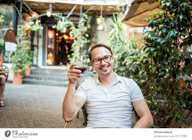 Man with wine glass sits in the chair and is happy 1 Person Young man Sit Day Exterior shot Warmth Summer Wine Wine glass Red wine Alcoholic drinks Drinking