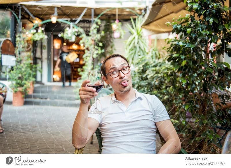 Man with wine glass sticks out his tongue 1 Person Young man Sit Day Exterior shot Warmth Summer Wine Wine glass Red wine Alcoholic drinks Drinking Toast