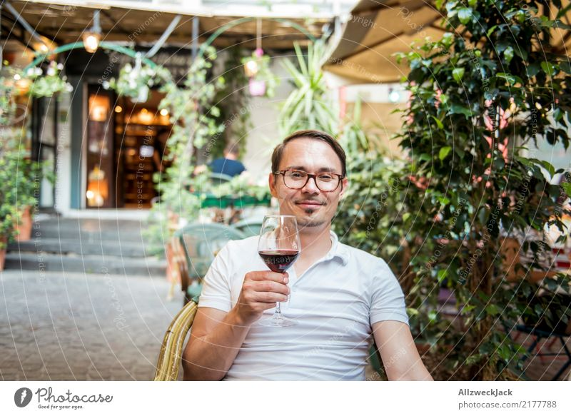 Man with wine glass sits in chair and is satisfied 1 Person Young man Sit Day Exterior shot Warmth Summer Wine Wine glass Red wine Alcoholic drinks Drinking
