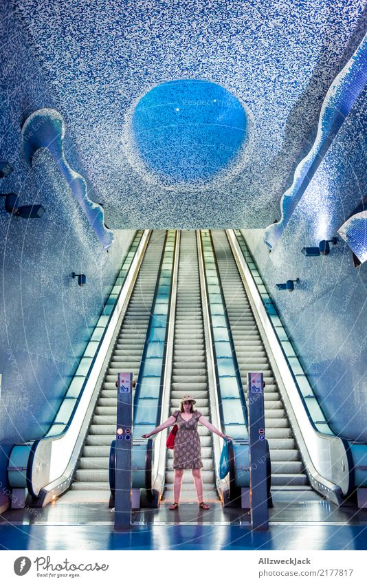 Woman standing or an escalator in the subway station Feminine Hat Dress Artificial light Underground Subsoil Escalator Stairs Tile Futurism Underwater photo