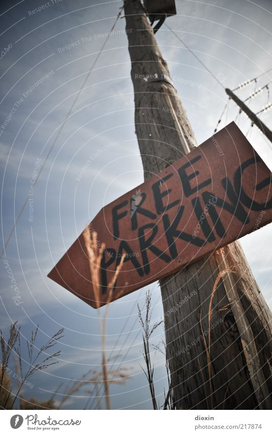 <--- FREE PARKING Electricity pylon Sky Clouds Weather Beautiful weather Plant Grass Parking lot Signs and labeling Pole Tall Handwritten Signal Signage