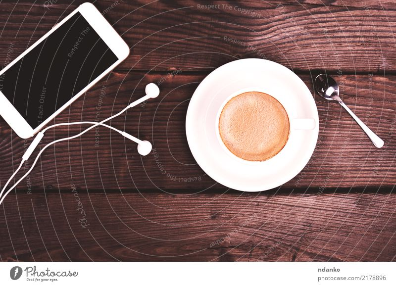 white cup with coffee and foam Colour White Black Natural Wood Brown Table Beverage Telephone Coffee Hot Restaurant Breakfast Café Headphones PDA