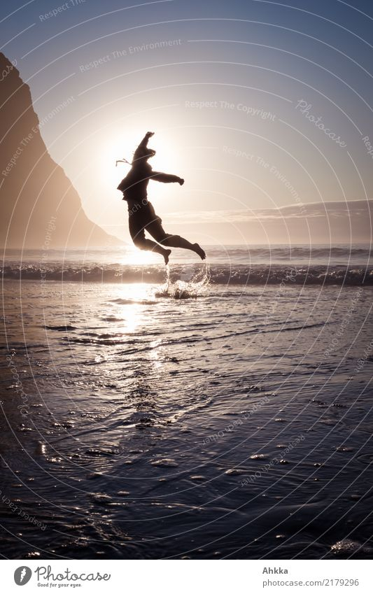 Young woman jumps out of the sea into the sunset Life Harmonious Contentment Senses Adventure Dance Youth (Young adults) Nature Cloudless sky Horizon Sun