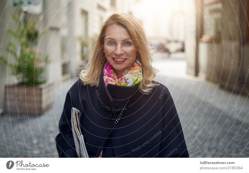 Blond mature smiling woman on street Elegant Happy Face Business Woman Adults 1 Human being 30 - 45 years Newspaper Magazine Pedestrian Street Coat Blonde