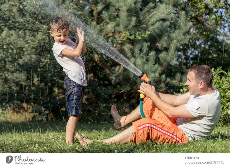 Happy father and son playing in the garden at the day time. People having fun oudoors. Concept of happy family. Lifestyle Joy Leisure and hobbies Playing
