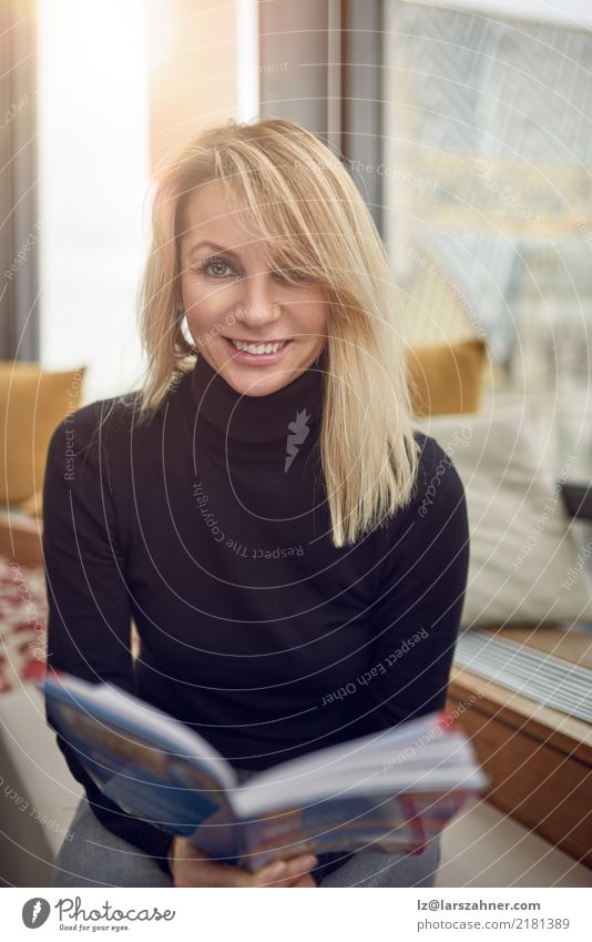 Smiling woman holding book while sitting down Happy Reading Tourism Woman Adults 1 Human being 30 - 45 years Book Blonde Sit Happiness Middle-aged inside