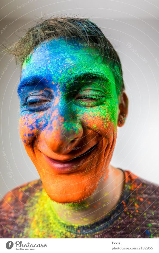 Man with Holi powder in face cartoon Multicoloured Laughter Smiling Crazy Perspective Holi Kino Powder Young man Face Blue Yellow Green Orange Nose Large