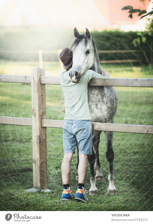 Young man hugs horse Lifestyle Human being Youth (Young adults) Nature Meadow Animal Horse Emotions Moody Pasture Fence Embrace Man Colour photo Exterior shot