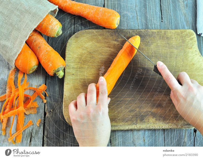 process of cutting fresh carrots Vegetable Nutrition Vegetarian diet Diet Juice Knives Body Table Arm Hand Nature Wood Fresh Natural Carrot background food