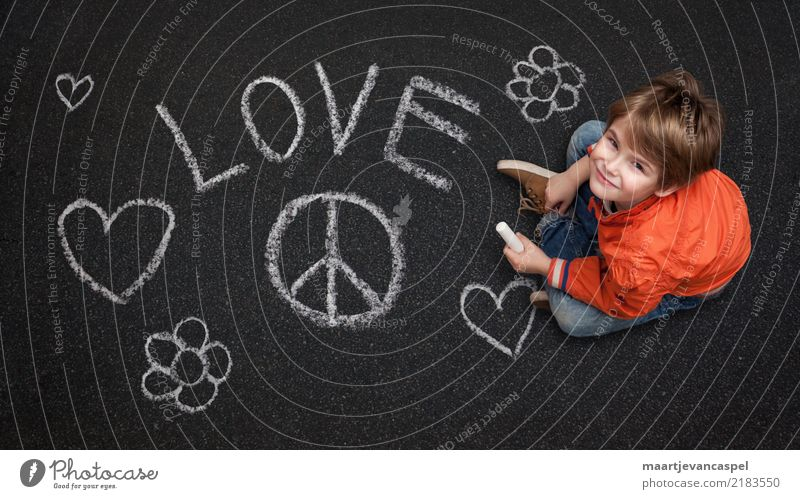 Boy with chalk wants peace and love Human being Masculine Child Boy (child) Infancy Life 1 3 - 8 years Street Jeans Chalk Chalk drawing Smiling Laughter Love