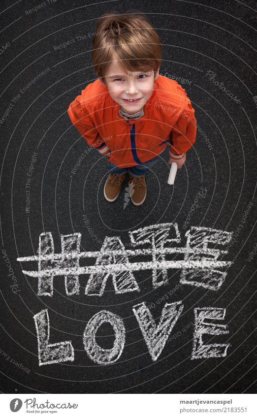 Boy with chalk doesn't want hate but love Human being Masculine Child Boy (child) Infancy Life 1 3 - 8 years Street Jeans Chalk Chalk drawing Smiling Love Write