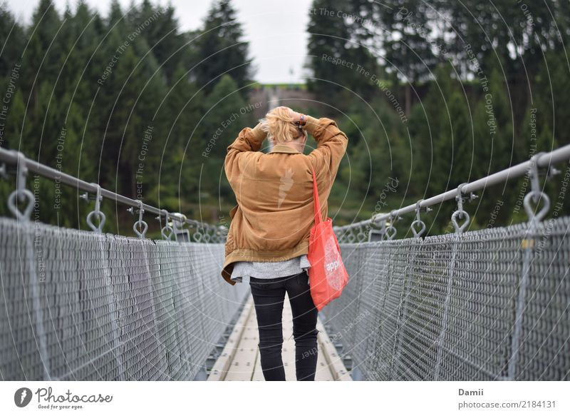 Youth (Young adults) Young woman Tree Forest Lanes & trails Hair and hairstyles Going To enjoy Bridge To go for a walk Jacket Steel cable Make Fir tree Bag