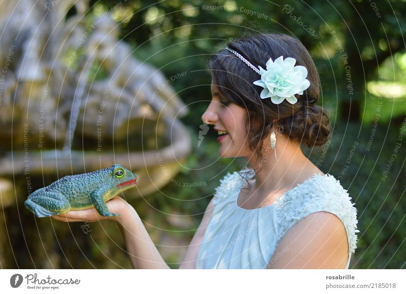 kiss me .... young brunette woman dressed like a princess looks skeptically at a frog on her hand and considers whether to kiss it Young woman Stage play