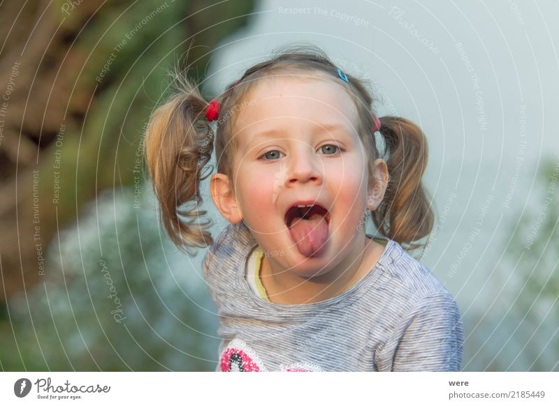 Little girl with blonde hair sticks out her tongue Playing Child Human being Feminine Toddler Head 1 3 - 8 years Infancy Brash Curiosity Cute Dirty Blonde
