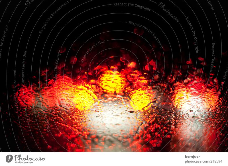 blurry vision Traffic jam Rain Rainwater Drops of water Windscreen Window pane Brake light Transport Highway Abstract Stand Motor vehicle Red Yellow Rear light