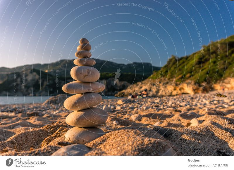 Stone pyramid on a sandy beach with mountains and water in the background Landscape Sand Water Cloudless sky Summer Beautiful weather Tree Bushes Beach Bay