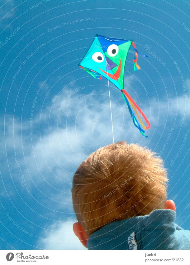 Child flying kites Colour photo Exterior shot Close-up Copy Space left Copy Space top Day Rear view Forward Sun Sky Clouds Wind North Sea Blue Brown Red