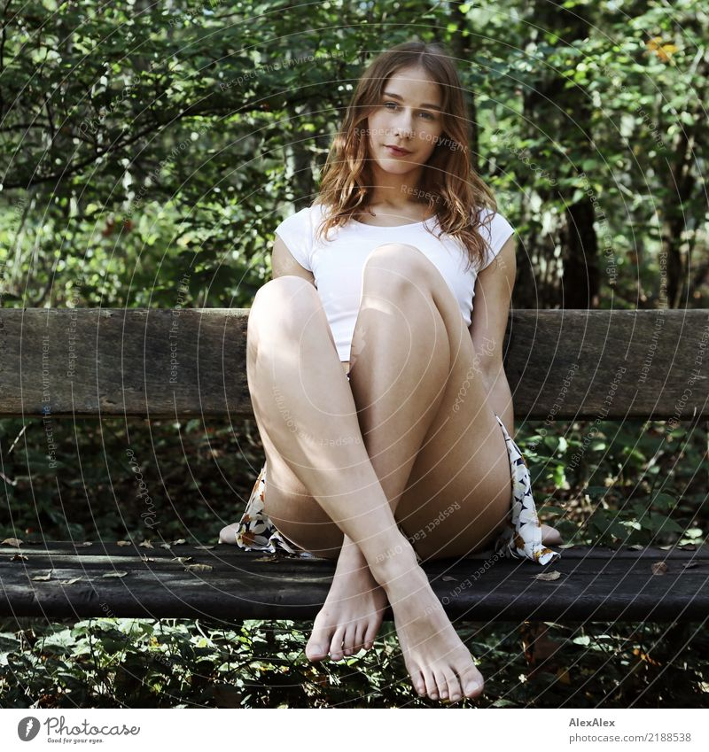 Young, very athletic woman in skirt and t-shirt sits barefoot on a wooden bench in the forest with her legs crossed Joy pretty Life Well-being Trip Adventure