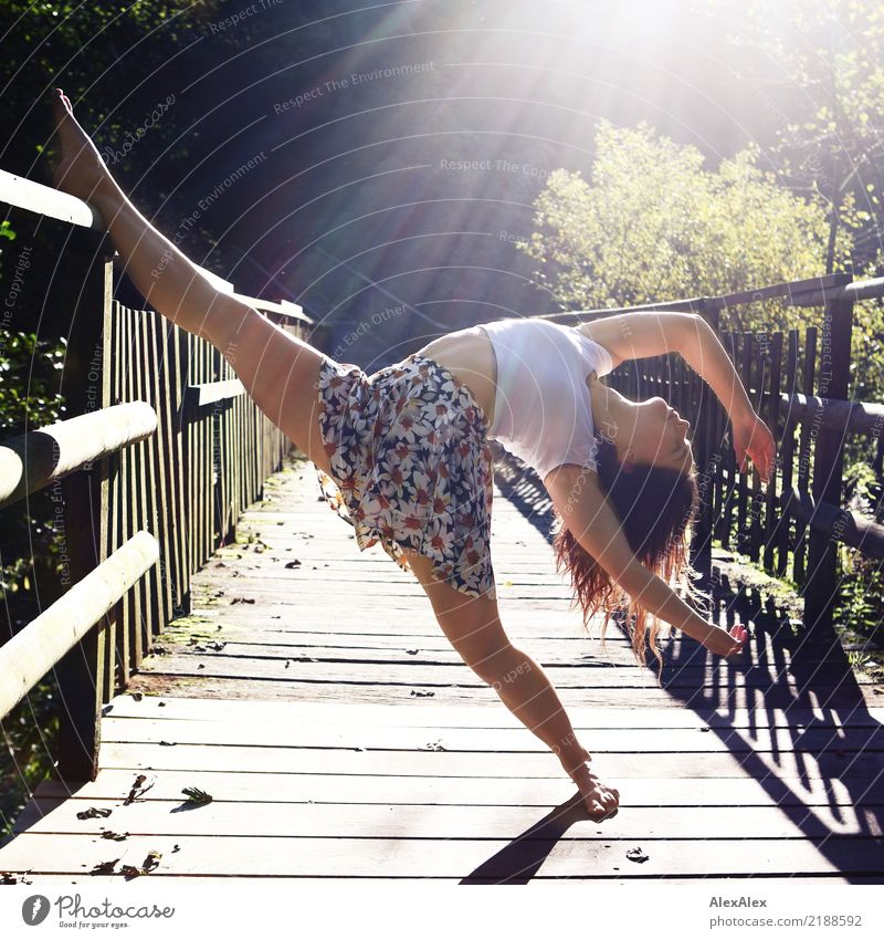 Young, very athletic woman stands barefoot on a wooden bridge in the backlight in the woods and leans one leg on the railing in the dance pose she is doing. She has a belly top on and is barefoot.