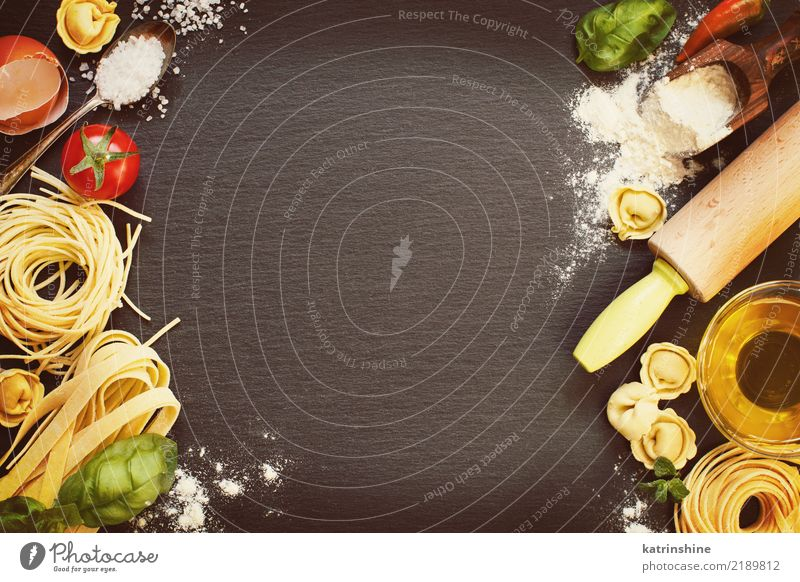 Fresh pasta and ingredients on a dark board top view Bottle Dark Yellow Red Basil Carbohydrate Cooking Dry Egg Flour Food Healthy Home-made Ingredients Italian