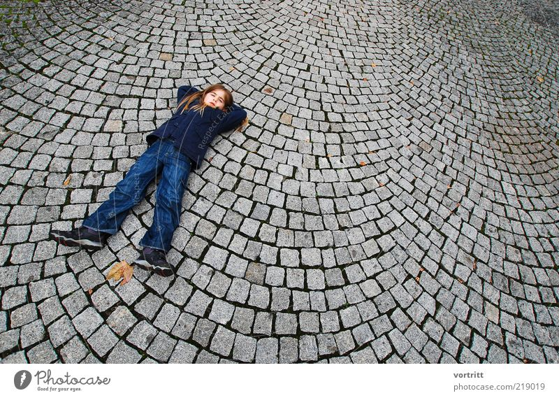 The girl with the long legs Human being Child Girl Infancy 1 3 - 8 years Places Pants Jacket Blonde Long-haired Stone Lie Blue Gray Paving stone Colour photo