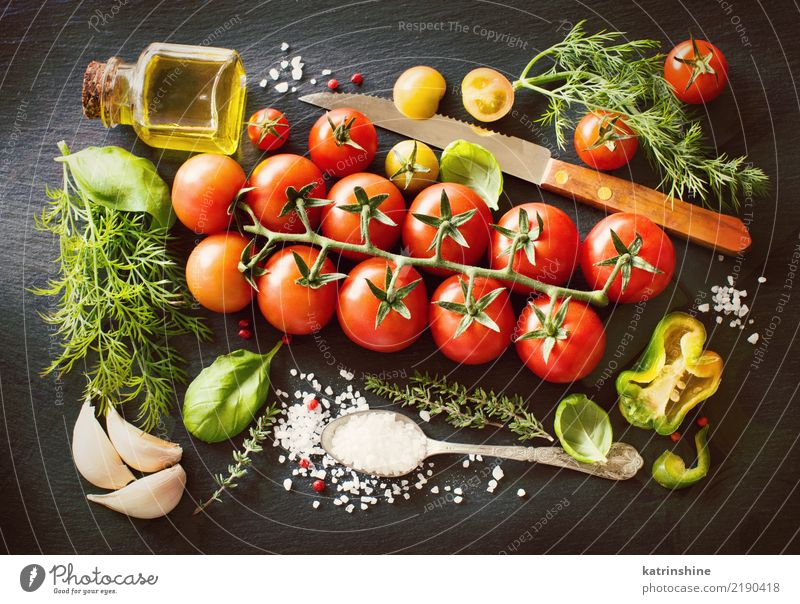 Cherry tomatoes, herbs and olive oil on a dark board Vegetable Vegetarian diet Diet Bottle Spoon Table Leaf Dark Fresh Bright Natural Green Red cook cooking