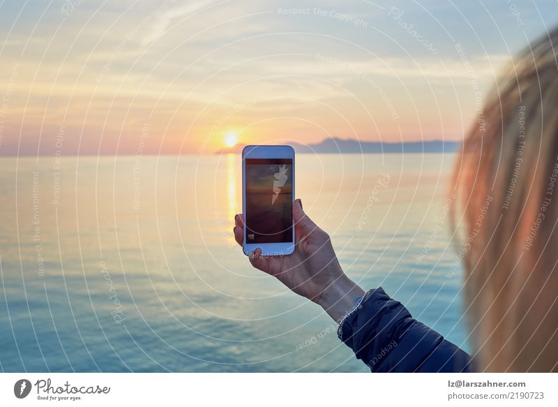Young woman taking a photo of a colorful ocean sunset Vacation & Travel Sightseeing Summer Sun Ocean Cellphone PDA Camera Technology Woman Adults 1 Human being