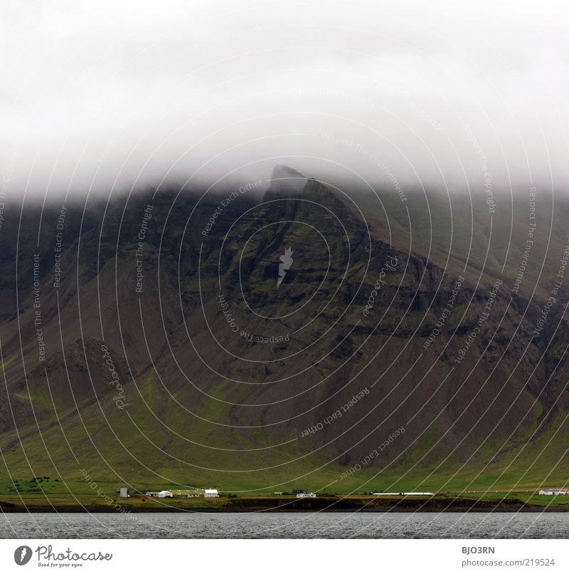 Berg's got a headache. Iceland. Fog Mountain Rock Stone Grass Gray Black Green House (Residential Structure) Inhabited Populated Coast Water Dreary Diffuse Low