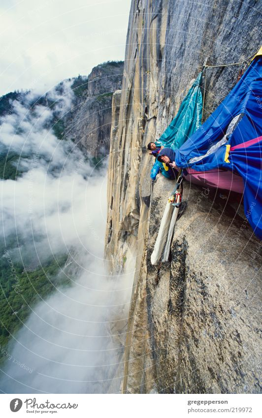 Rock climbing team bivouaced in a storm. Human being Adults Sports Friendship Tall Wet Adventure Rope Peak Climbing Trust Storm Athletic Risk Balance Fear of heights