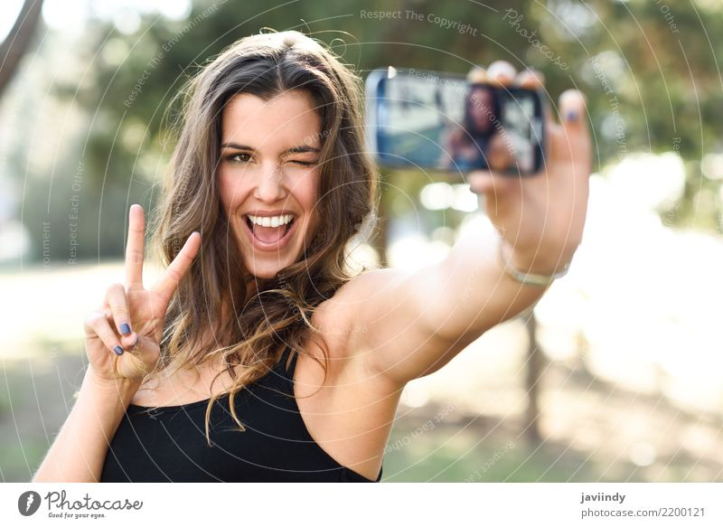 young woman selfie in the park with a smartphone doing v sign Joy Happy Beautiful Face Cellphone Camera Technology Human being Woman Adults Hand Fingers Smiling