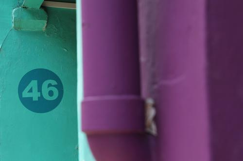 46 Wall (barrier) Wall (building) Digits and numbers House number Turquoise Violet Conduit Drainpipe Colour photo Exterior shot Blur Eaves Multicoloured