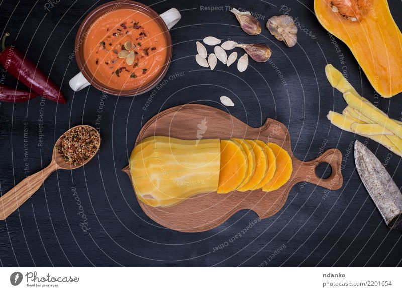 fresh pumpkin sliced into pieces Vegetable Soup Stew Eating Dinner Organic produce Vegetarian diet Knives Spoon Table Hallowe'en Nature Autumn Wood Fresh Above