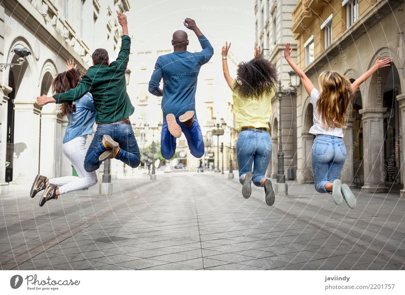 Multiracial group of people jumping together. Rear view. Woman Man Summer Beautiful Joy Adults Street Lifestyle Laughter Happy Group Together Friendship Jump