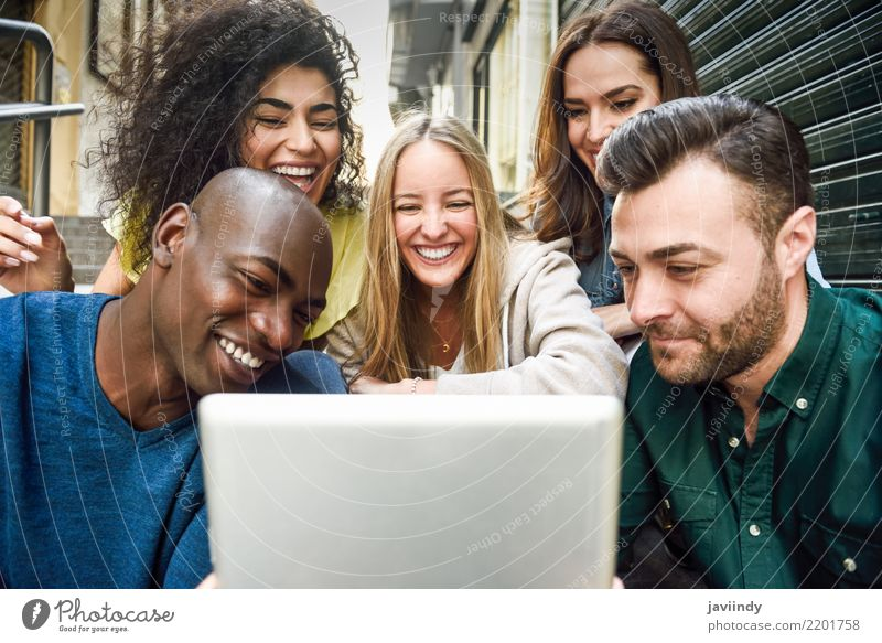 Multiracial young people looking at a tablet computer Woman Man Beautiful Joy Adults Street Lifestyle Laughter Happy Group Together Friendship Smiling Clothing