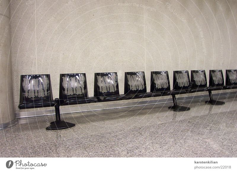 in series Waiting area Row of seats Black Gray Concrete wall Sterile Impersonal Cold Departure lounge Bench Room