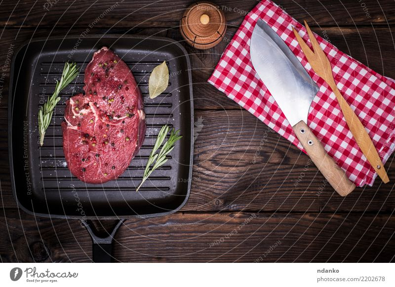 raw beef steak with spices Food Meat Herbs and spices Dinner Knives Fork Table Kitchen Wood Eating Fresh Green Red frying pan knife napkin Meal pepper Beef Chop
