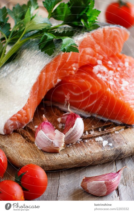 Fresh raw salmon on a wooden cutting board Red Eating Nutrition Table Fish Herbs and spices Vegetable Dinner Meal Diet Cooking Slice Tomato Raw Ingredients