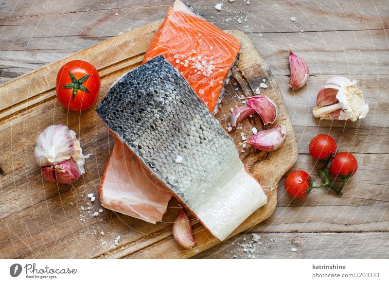 Fresh raw salmon and vegetables on a wooden cutting board Fish Seafood Vegetable Herbs and spices Nutrition Eating Dinner Diet Table Above Red background