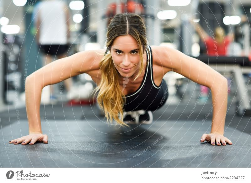 Young beautiful woman doing pushups in the gym. Lifestyle Body Sports Fitness Sports Training Human being Woman Adults 1 18 - 30 years Youth (Young adults)
